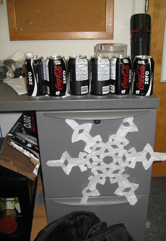 This oversized snowflake drew power from the filing cabinet and its Dark Contents. The filing cabinet already served as an altar, receiving daily offerings of Coke Zero tainted aluminum.